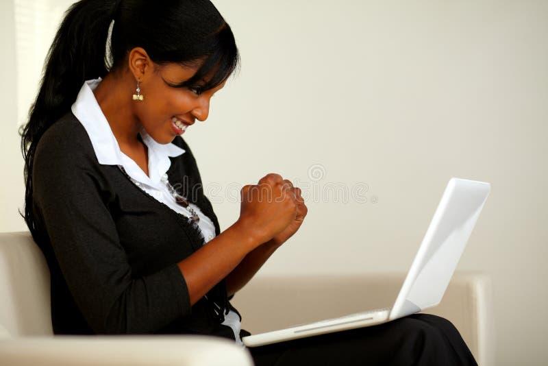 Donna attraente sul vestito nero con un computer portatile immagini stock