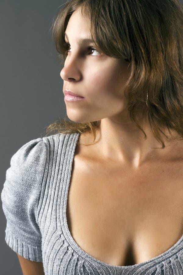 Donna attraente in un vestito lavorato a maglia grigio fotografie stock