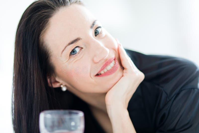 Donna attraente vestita in vino rosso bevente nero immagini stock libere da diritti