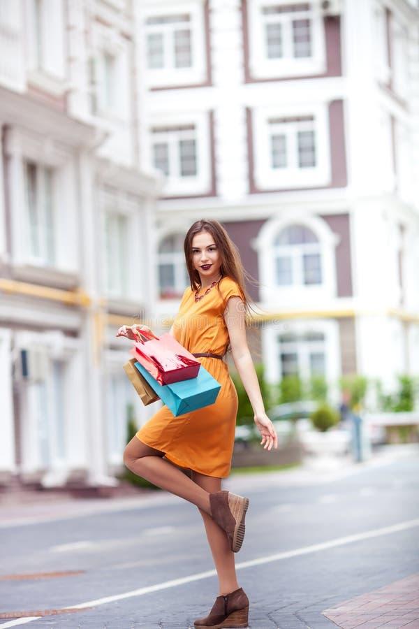 Donna attraente in vestito luminoso con i sacchetti della spesa nel ctiy fotografia stock