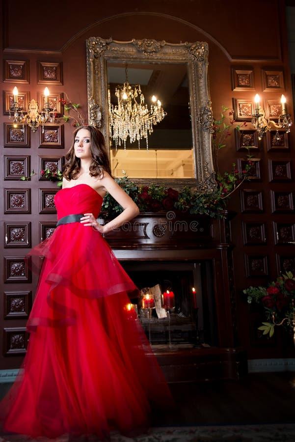 Donna attraente in vestito rosso lungo nell'interno di lusso retro, stile d'annata immagini stock libere da diritti