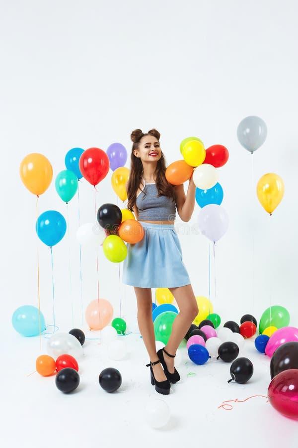 Donna in attrezzatura alla moda che posa con i palloni al partito luminoso immagini stock
