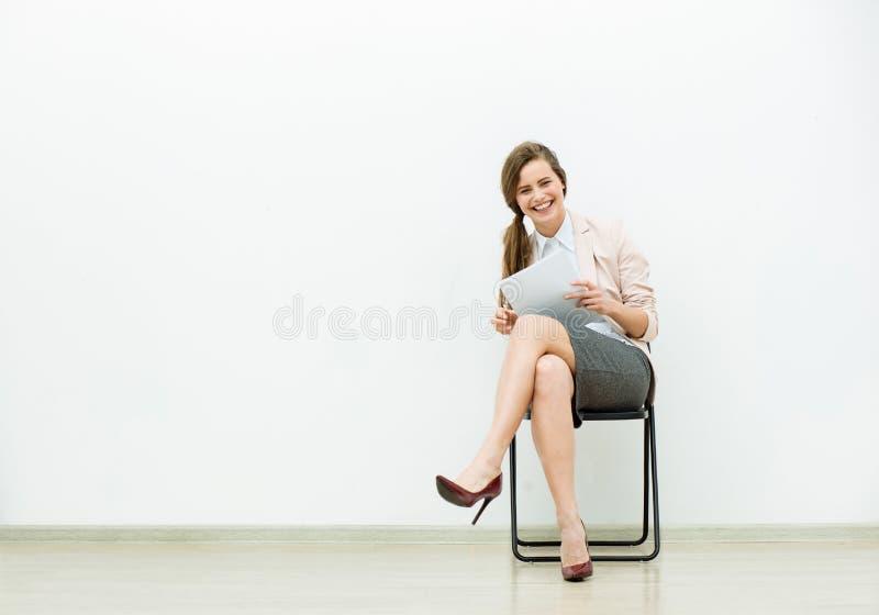 Donna in attrezzatura dell'ufficio che aspetta su una sedia immagine stock libera da diritti