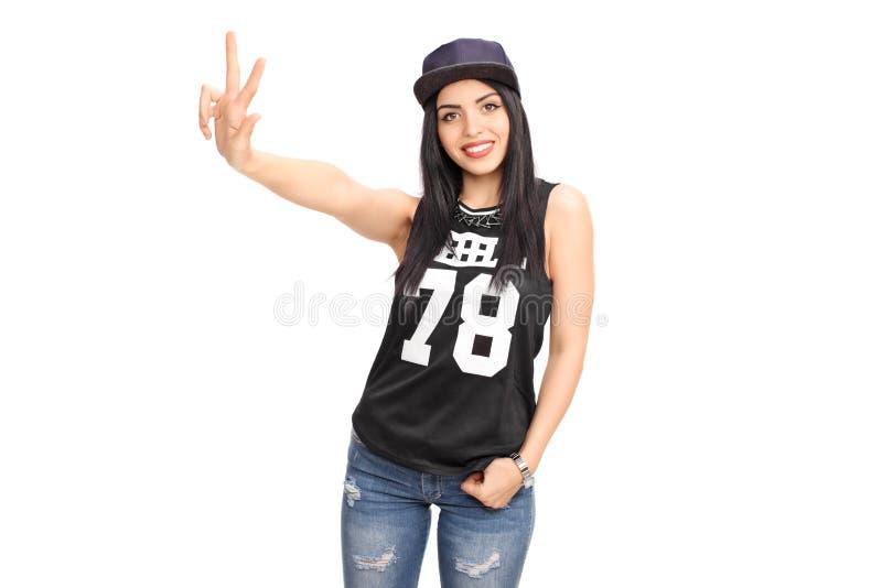 Donna in attrezzatura hip-hop che fa un segno della mano fotografia stock libera da diritti