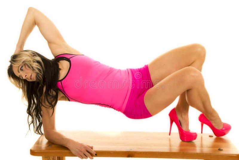 Donna in attrezzatura rosa sui piedi ed in gomito sul banco immagine stock libera da diritti