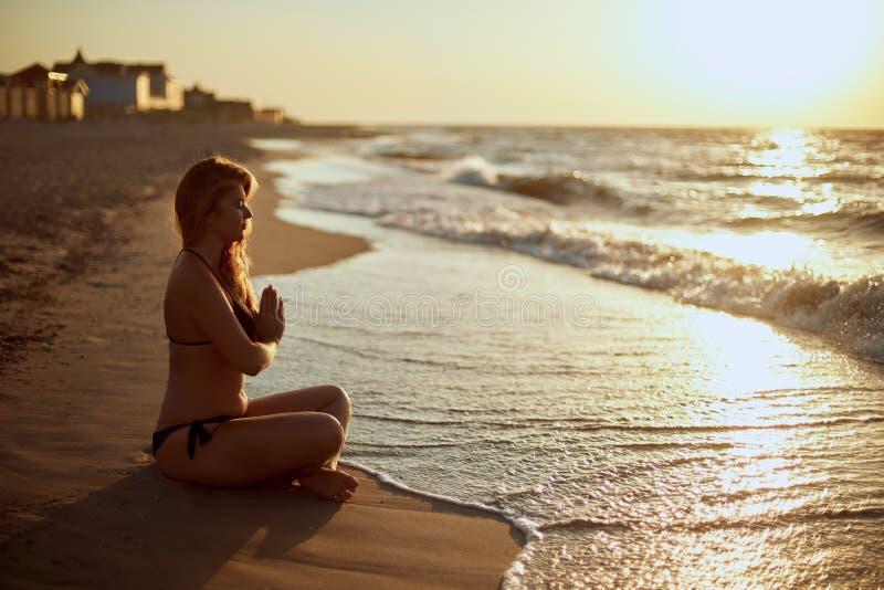 Donna autentica in costume da bagno che fa padmasana di yoga sulla spiaggia di mattina Siluetta unretouched reale della ragazza d fotografie stock libere da diritti
