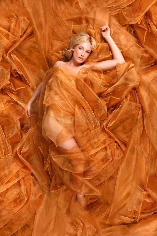 Donna avvolta nel tessuto scorrente del rame immagini stock