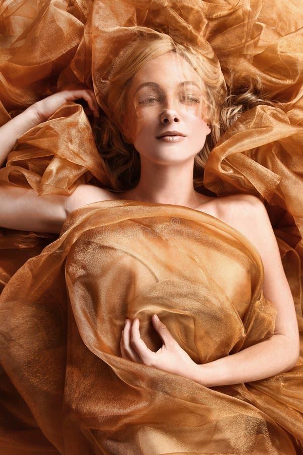 Donna avvolta nel tessuto scorrente del rame fotografia stock libera da diritti