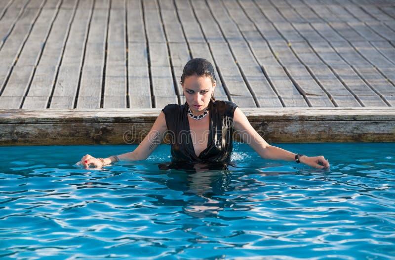 Donna bagnata in vestito nero in una piscina immagini stock