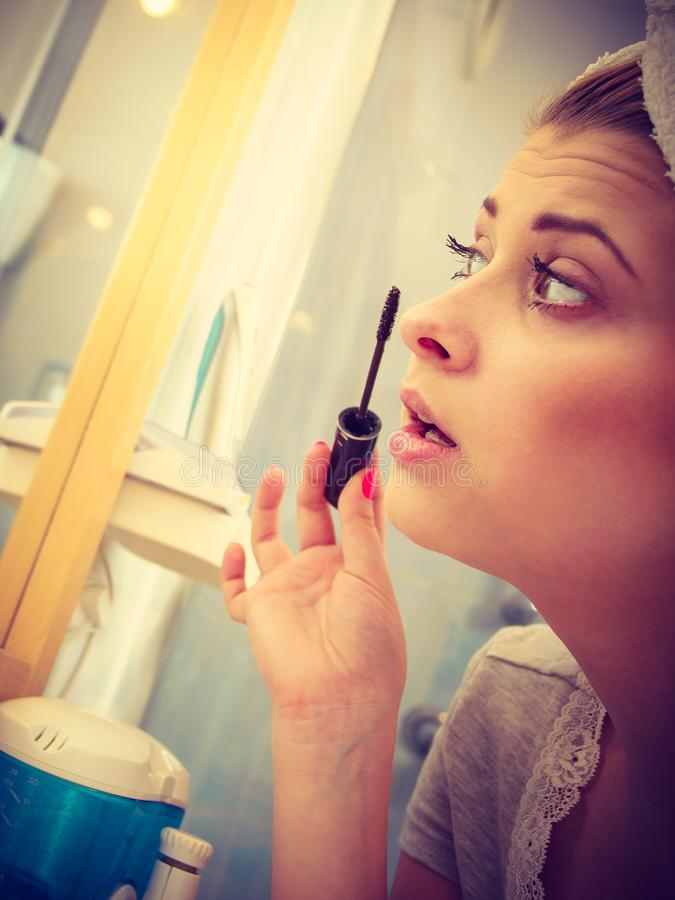 Donna in bagno che applica mascara sui cigli fotografia stock
