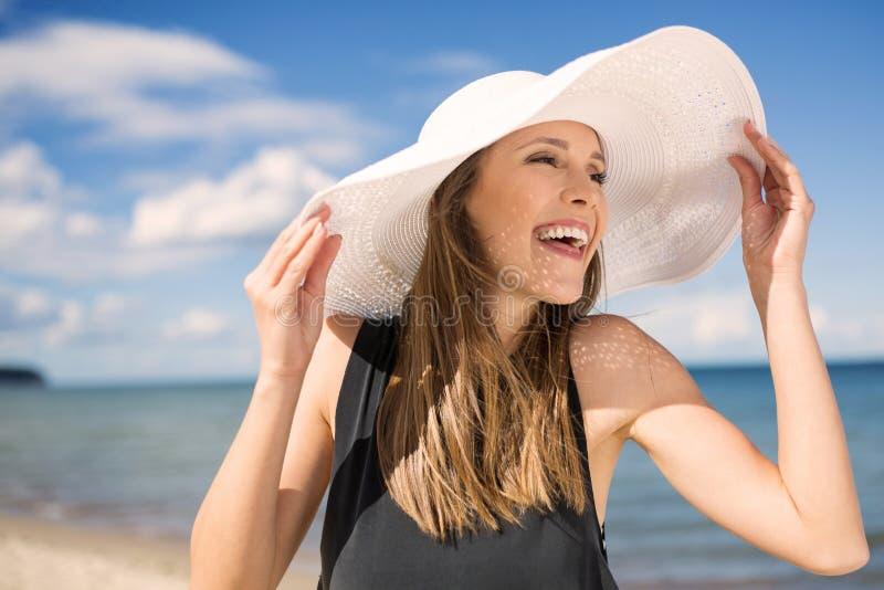 Donna bella in cappello sulla spiaggia che ride e che distoglie lo sguardo fotografia stock libera da diritti
