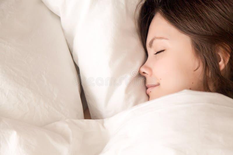 Donna bella che dorme nel letto accogliente, vista superiore di colpo in testa del primo piano immagini stock libere da diritti
