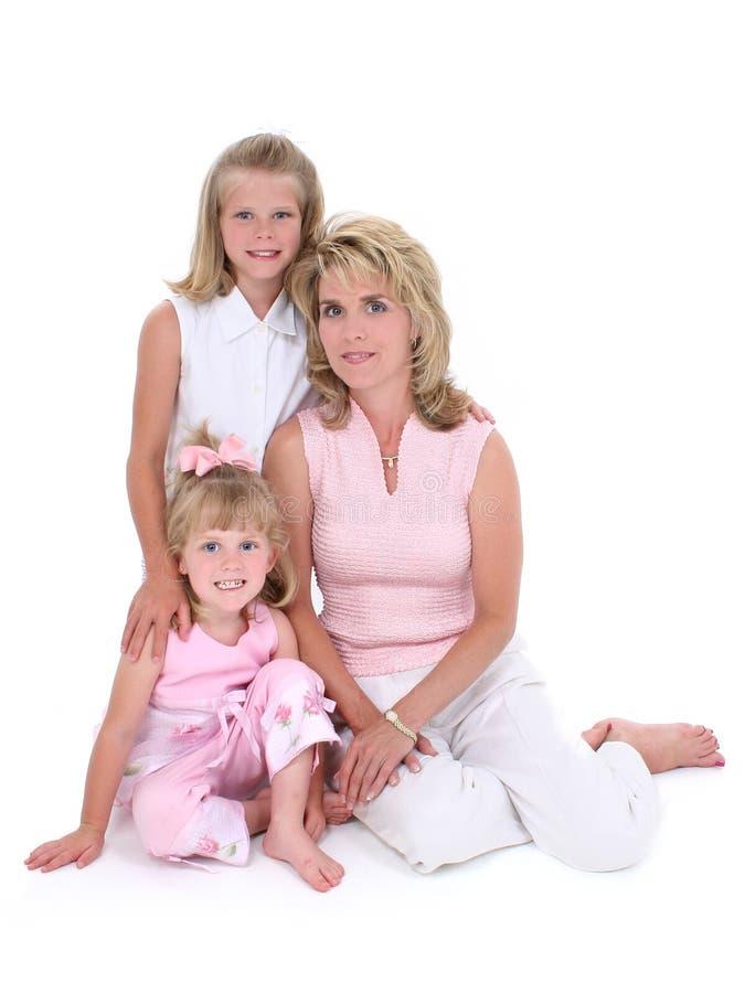Donna bella con le sue figlie sopra bianco immagine stock