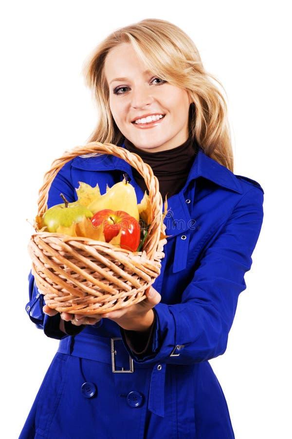 Donna bella con un cestino di frutta matura immagine stock