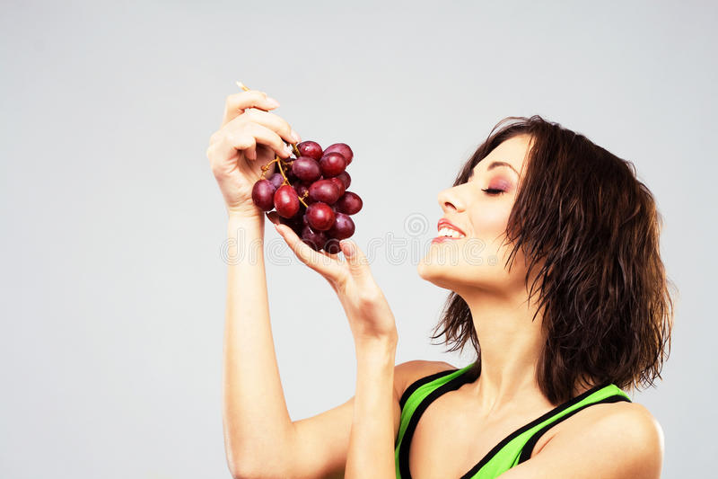 Donna bella con un mazzo di uva immagini stock libere da diritti