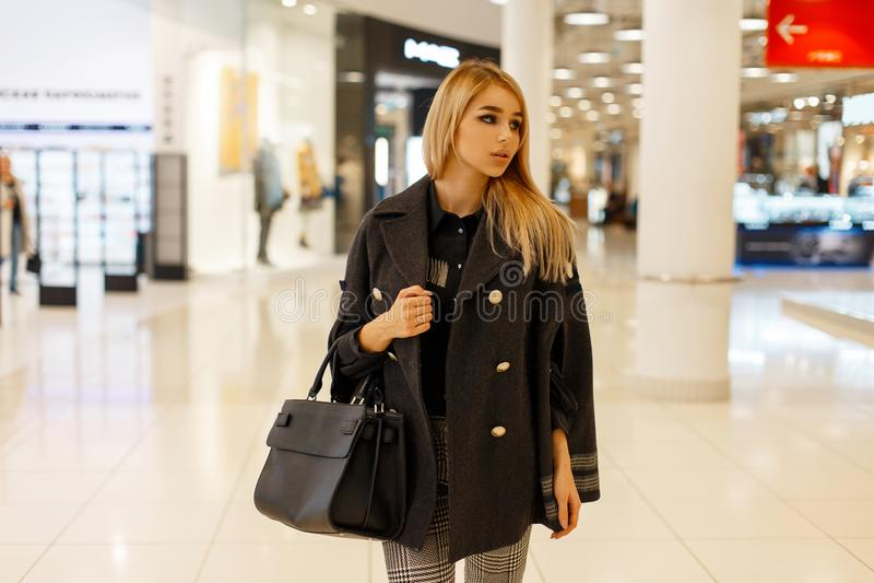 Donna bella con una borsa di modo in un cappotto alla moda d'avanguardia fotografia stock