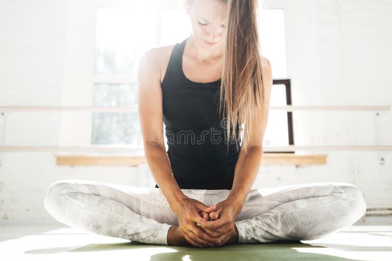 Donna bella di misura che fa allungando esercizio che si siede sulla stuoia di yoga in gomma bianca soleggiata fotografia stock libera da diritti