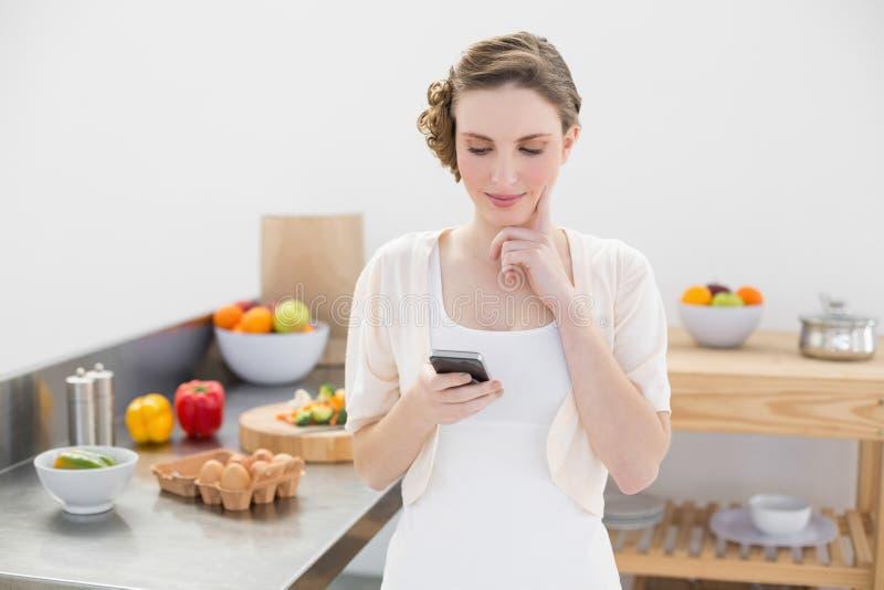 Donna bella di pensiero che utilizza il suo smartphone che sta nella cucina fotografie stock