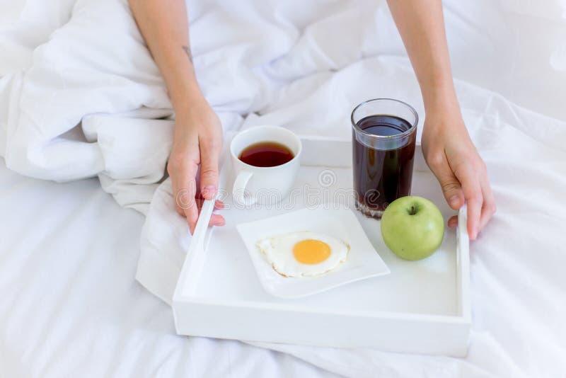 Donna bella giovane che mangia prima colazione in base immagini stock