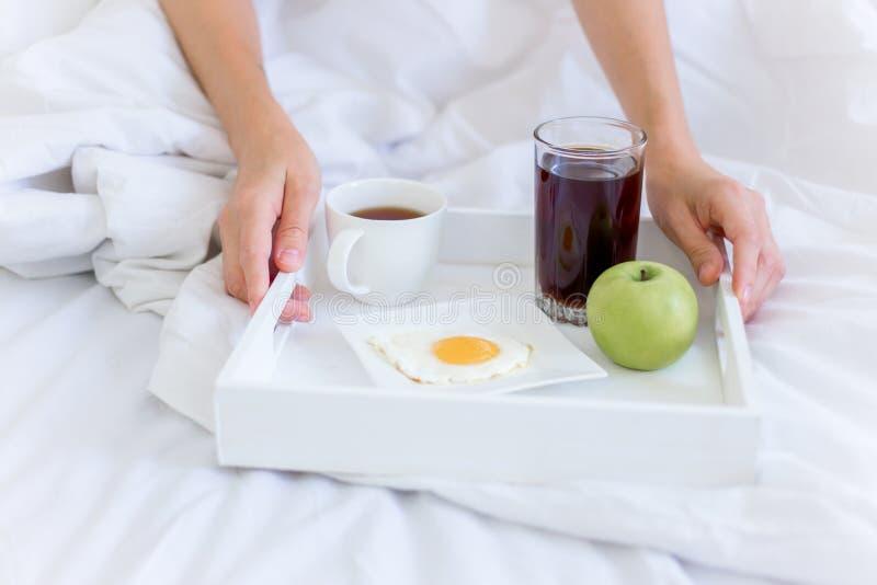 Donna bella giovane che mangia prima colazione in base immagine stock
