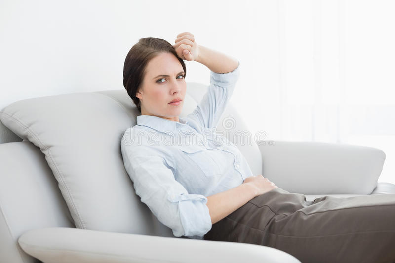 Donna ben vestito seria che si siede sul sofà immagine stock libera da diritti