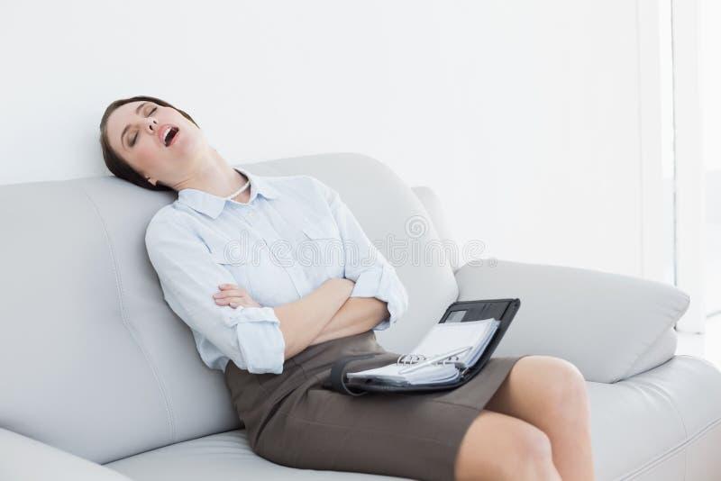 Donna ben vestito stanca che si siede e che dorme sul sofà fotografia stock libera da diritti