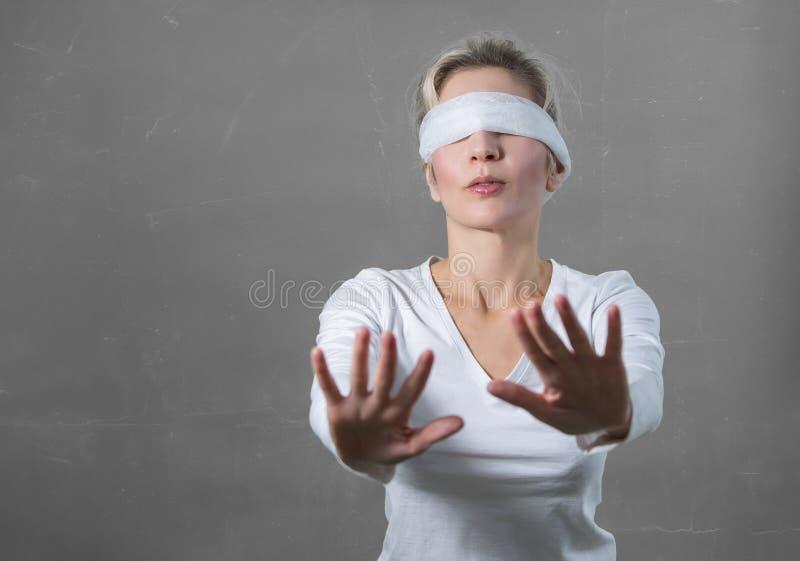 Donna bendata gli occhi con le mani che raggiungono in avanti fotografie stock