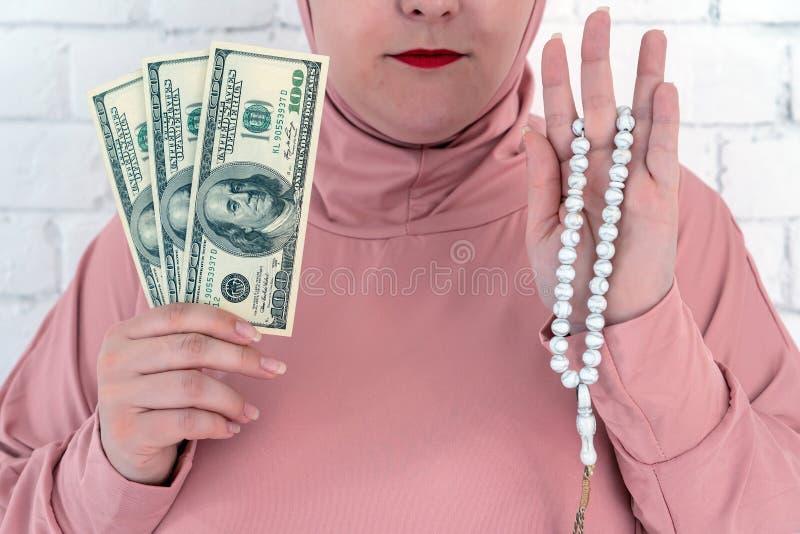 Donna bianca con gli occhi azzurri in un hijab rosa che tiene un rosario ed i dollari su un fondo bianco fotografie stock libere da diritti