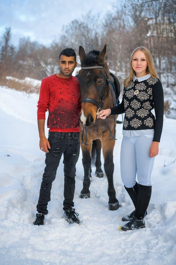 Donna bianca ed uomo arabo accanto al cavallo nell'inverno, coppia internazionale immagini stock