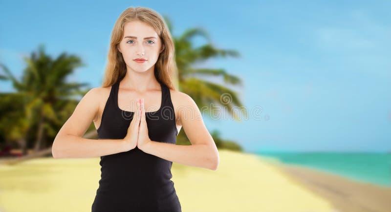 Donna bianca messa a fuoco che fa gesto di mudra del namaste davanti al mare di estate immagine stock