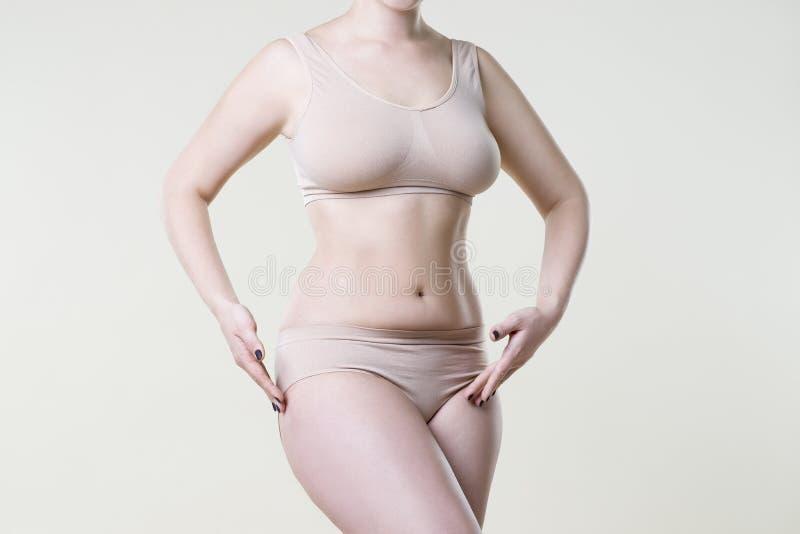 Donna in biancheria intima beige sul fondo dello studio, cellulite sull'ente femminile fotografie stock libere da diritti