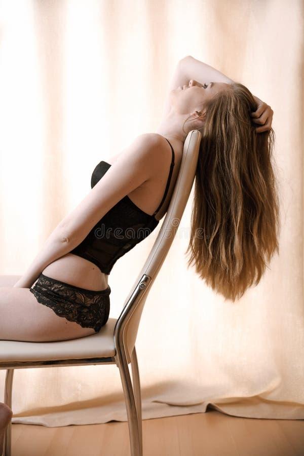 Donna In Biancheria Nera Che Si Siede Su Una Sedia Con I ...