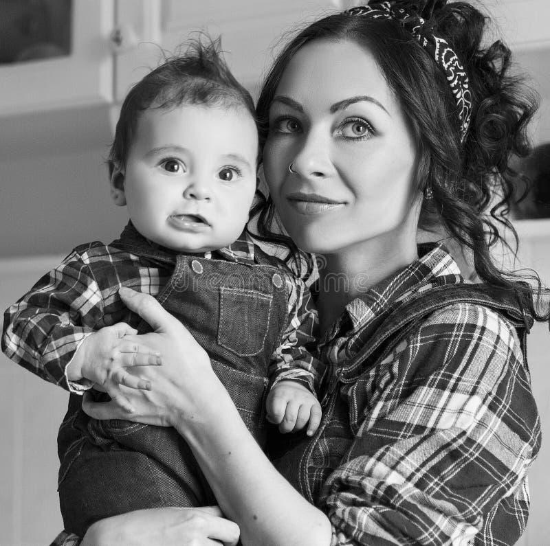 Donna in bianco e nero del ritratto della famiglia con il bambino nella cucina immagine stock libera da diritti