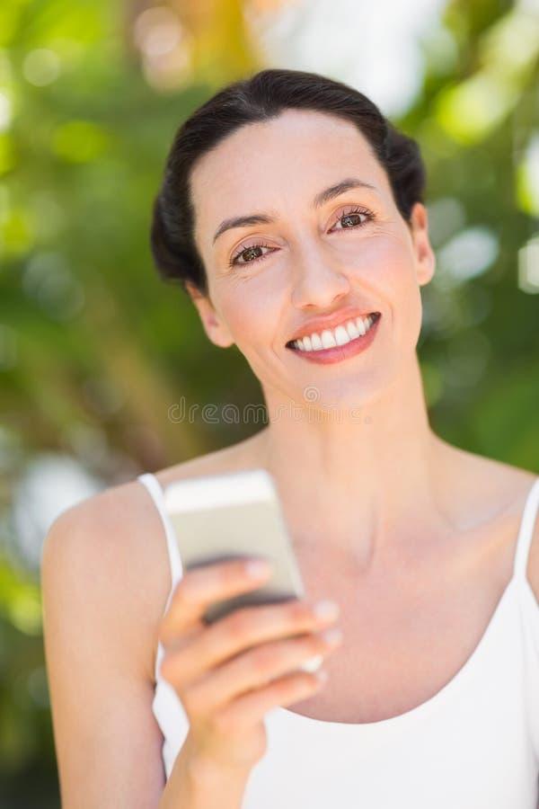 donna in bianco esaminando il suo telefono fotografie stock libere da diritti