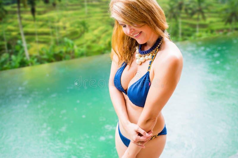 Donna in bikini blu dallo stagno immagini stock libere da diritti