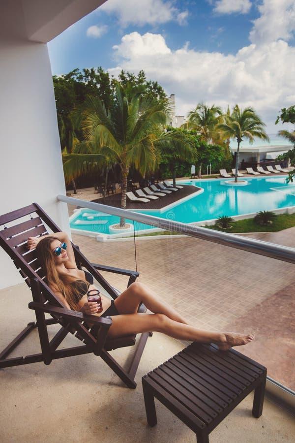 Donna in bikini che beve un cocktail sul terrazzo fotografia stock