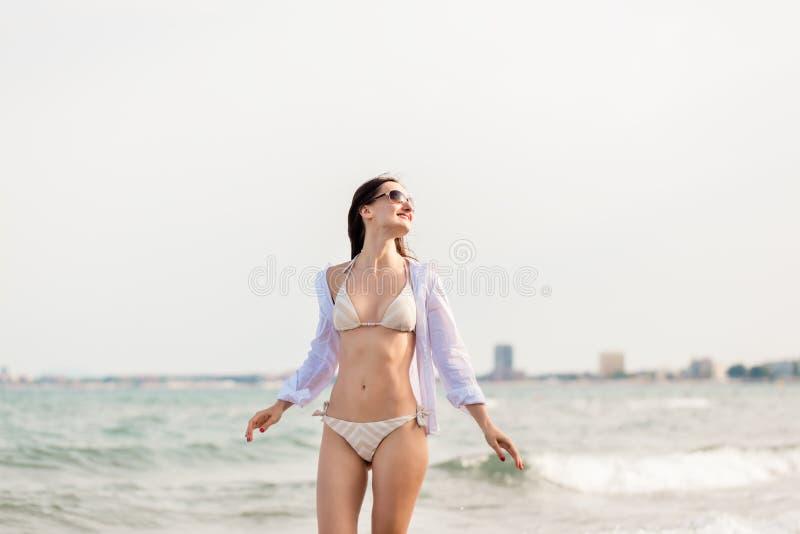 Donna in bikini che cammina giù la spiaggia nelle sue vacanze estive fotografie stock libere da diritti