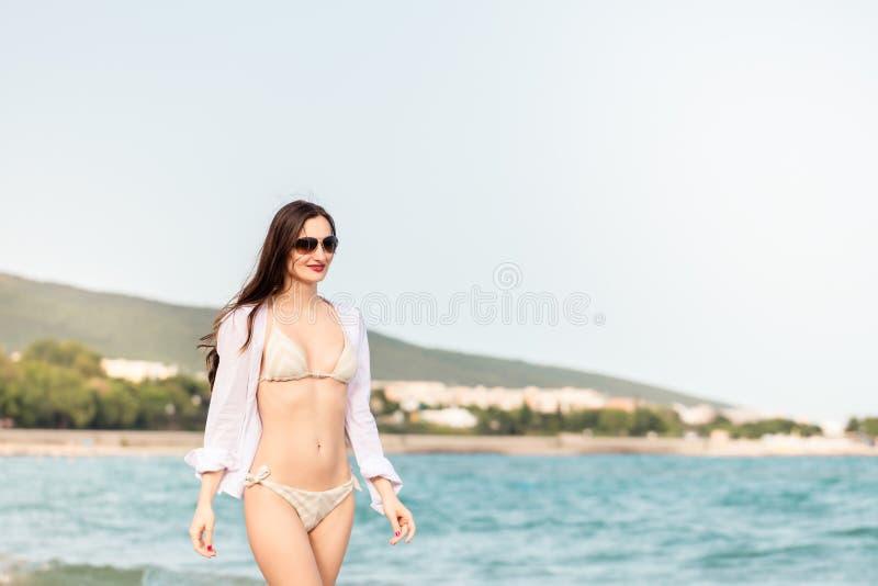 Donna in bikini che cammina giù la spiaggia nelle sue vacanze estive immagine stock libera da diritti