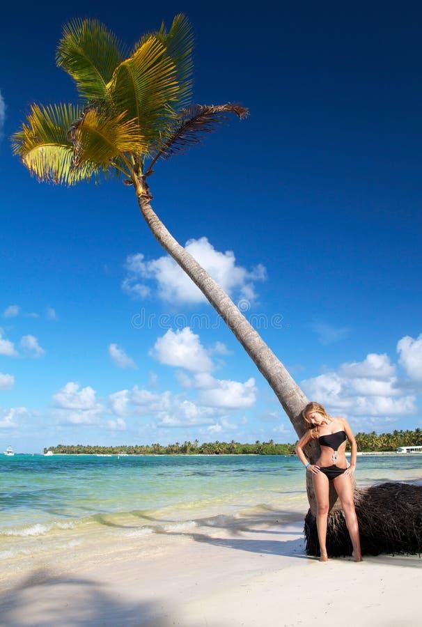 Donna in bikini che si distende sulla spiaggia caraibica immagini stock libere da diritti