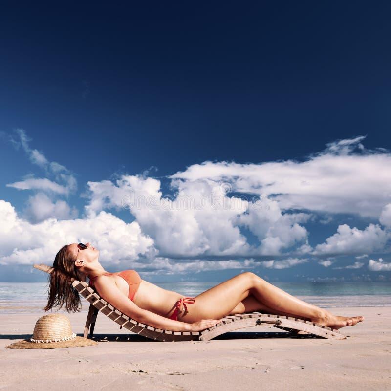 Donna in bikini che si trova sulla spiaggia alle Seychelles fotografie stock