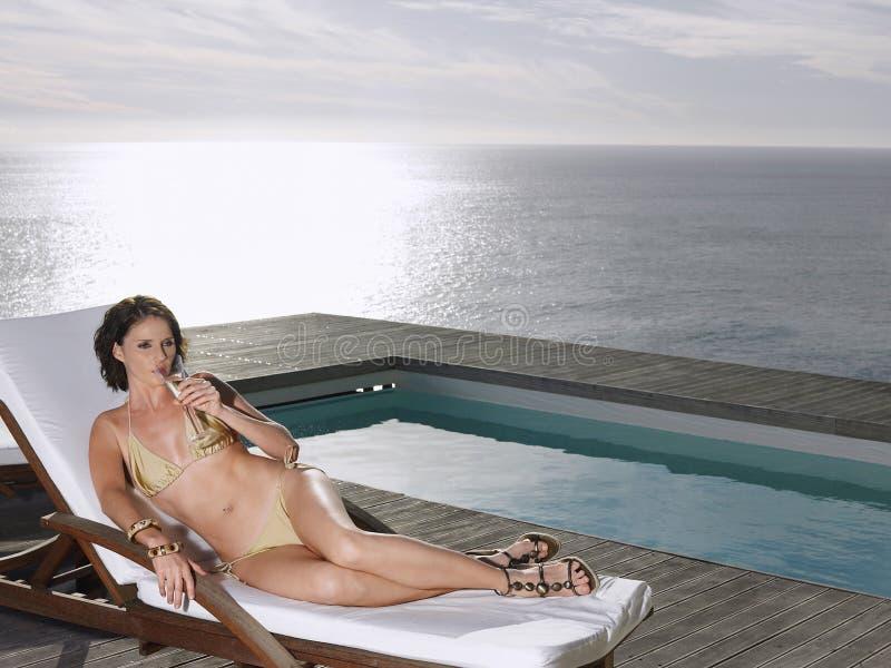 Donna in bikini che sorseggia Champagne At Poolside By Ocean fotografie stock