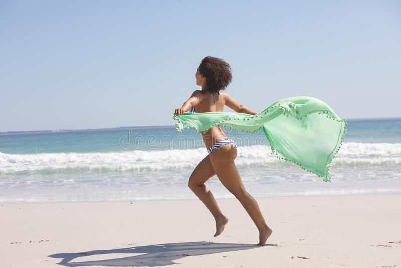 Donna in bikini con la sciarpa che corre sulla spiaggia fotografia stock libera da diritti