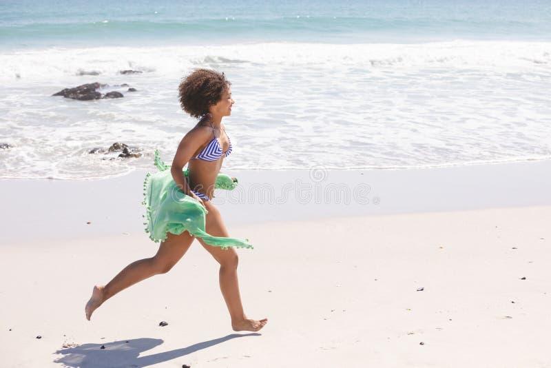 Donna in bikini con la sciarpa che corre sulla spiaggia immagine stock libera da diritti