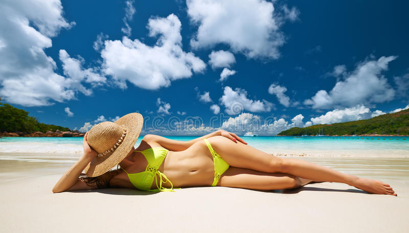Donna in bikini giallo che si trova sulla spiaggia alle Seychelles fotografia stock