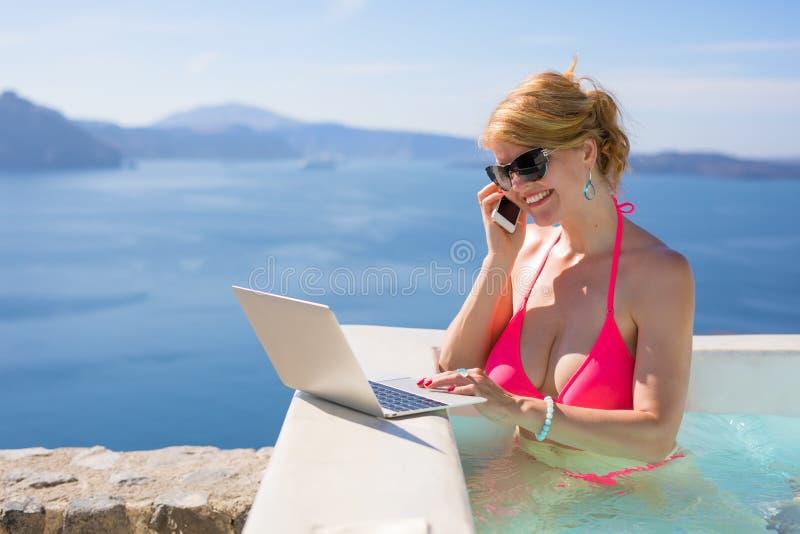 Donna in bikini rosa che lavora al computer portatile e che parla sul telefono cellulare immagini stock
