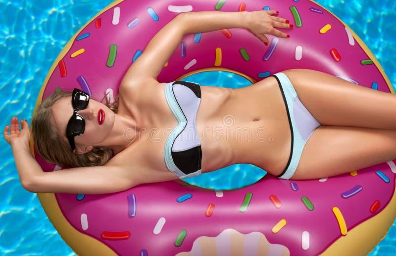 Donna in bikini sul materasso gonfiabile nella piscina immagine stock libera da diritti