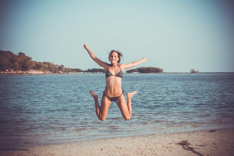 Donna in bikini sulla spiaggia che salta sotto l'acqua immagine stock