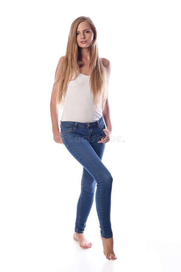 Donna bionda abbastanza dai capelli lunghi dei giovani che posa in abbigliamento casual su fondo bianco in uno studio Foto di est fotografia stock libera da diritti