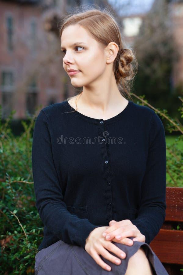 Donna bionda abbastanza giovane che si siede sul banco immagine stock