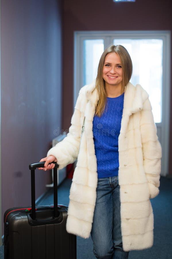 Donna bionda abbastanza giovane che viaggia portando un cappotto, jeans che tirano una cassa del vestito immagine stock libera da diritti